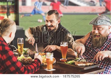 Enjoying dish. Cheerful friends watching football while eating meat and drinking cool beer. They sitting in pub with smile