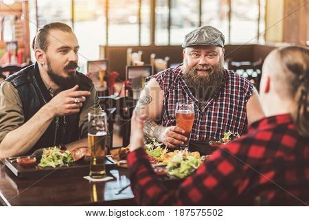 Very joyful evening. Confident adult men having fun in bar. They communicate while enjoying their meal