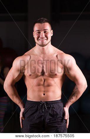 Young handsome muscular man bodybuilder posing in gym