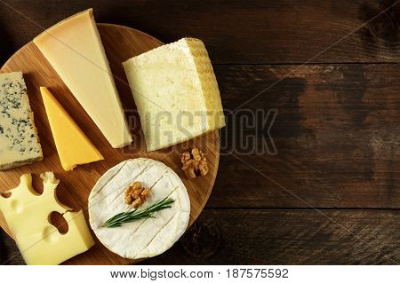 An overhead photo of a selection of cheeses, shot from above on a dark rustic texture, with a place for text