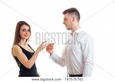 beautiful romantic couple standing beside smiling and carrying white wine glasses isolated on white background