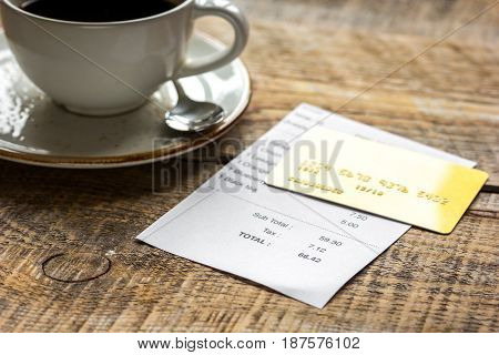 restaurant bill, credit card and coffee on wooden table background