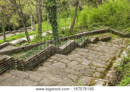 Paths with stairs in park covered with stone slabs in springtime