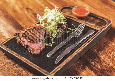 Just meat. Close-up of appetizing tasty grilled steak, fresh salad and red sauce served with fork and knife. Wooden table in the background