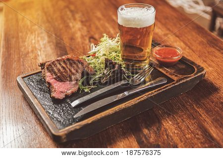 Delicious meal. Close-up of juicy appetizing grilled steak with mix salad, red sauce and glass of light beer served on wooden table