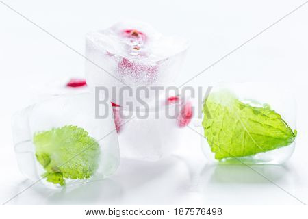 Ice cubes with fresh berries and mint for summer drink on white table background