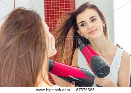 joyful charming girl looks in the mirror and dries hair closeup