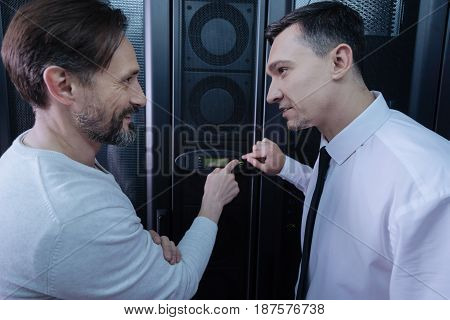 Press it. Handsome nice positive men looking at each other and pointing at the button on the control panel while intending to press it