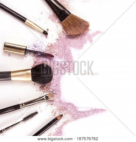 Makeup brushes, lip gloss and pencil on white background, with traces of powder and blush forming a frame. A square template for a makeup artist's business card or flyer design, with copyspace