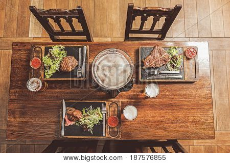 Restaurant food. Top view of meat dishes served at wooden table. T-bone steak, medallion and roast beef fillet with salad and sauce with beer dispenser and glasses are on desk