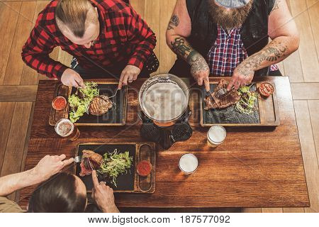 Delicious food. Top view of men eating meat and drinking cold beer. They sitting around table while enjoying their dishes