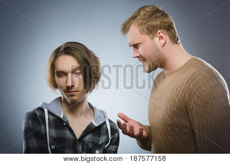 Evil man yelling at the teenager. The elder brother scolds the younger. isolated on gray background