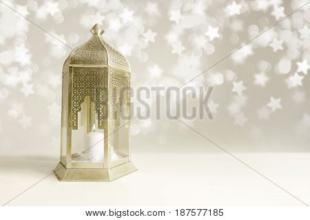 Ornamental golden Arabic lantern on the table with glittering star-shaped bokeh lights. Greeting card for Muslim community holy month Ramadan Kareem, festive blurred background with empty space.