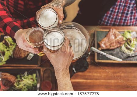 Cheers. Top view close up of cups with beer stretched out by friends in pub. Wooden table with meat dishes in the background