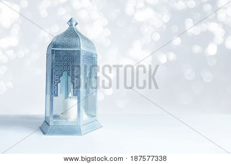Ornamental silver and blue Arabic lantern on the table with glittering bokeh lights. Greeting card for Muslim community holy month Ramadan Kareem, festive blurred background with a lot of empty space.