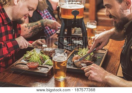 Have some entertainment. Three cheerful guys enjoying beer and grilled meat. They sitting in sports bar