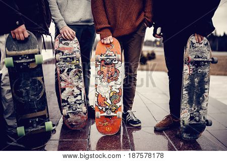 Moscow, Russia - May 20, 2017: Friends of the men's company hold their hands skateboards. Concept group of street athletes students