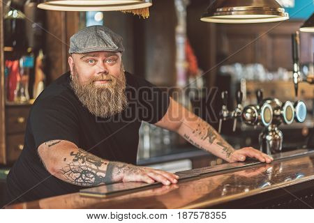 Waiting. Portrait of serious fat bartender leaning on bar counter. He looking at camera thoughtfully