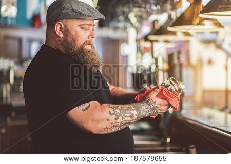 Concentrated at work. Tattooed adult bartender wiping glass diligently. He standing at bar counter and looking at mug
