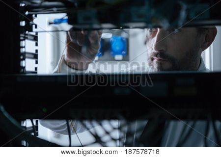 Network system. Professional handsome system administrator standing near the server rack and checking holding an internet cable while checking the network system
