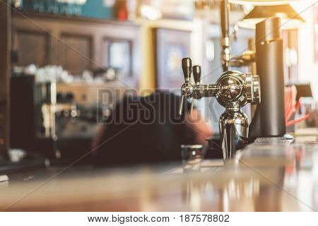 Bar counter. Close-up of modern beer taps in pub. Barman laboring in the background