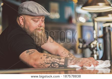 Lost in thoughts. Fat male bartender expressing thoughtfulness while leaning on workplace in pub. He is wiping bar counter pensively