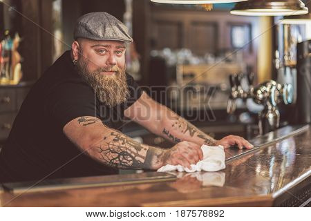 Be positive. Joyful tapster cleaning work surface in pub. He looking at camera cheerfully
