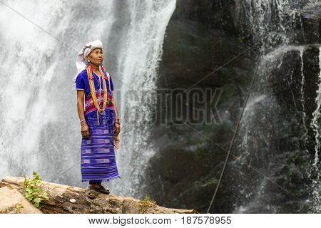 MAE KLANG LUANG, THAILAND - FEBRUARY 18, 2017 : A karen tribe woman in traditional dress is standing near the Pha Dok Seaw waterfall near the Mae Klang Luang village, Thailand