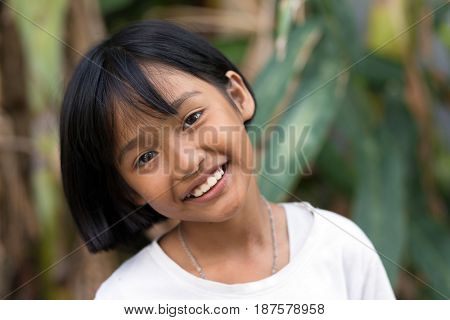 PHUKET TOWN, THAILAND - MARCH 11, 2017 : Portrait of an orphan little girl smiling at the camera, Phuket, Thailand