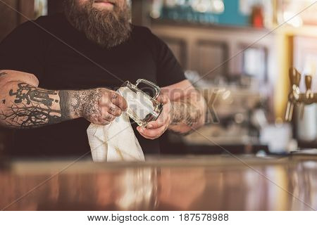 Time to work. Adult tattooed barman wiping glass while standing at counter. Focus on his hands