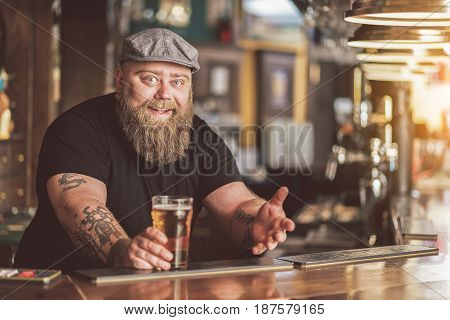 Special offer. Portrait of cheerful bearded bartender leaning on counter with smile while holding cold light lager. He looking at camera with joy