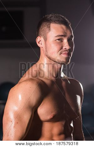 Young handsome muscular man bodybuilder posing in gym