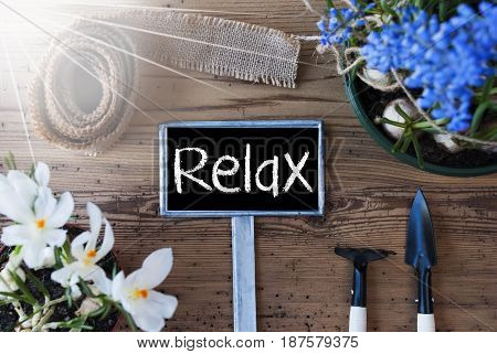 Sign With English Text Relax. Sunny Spring Flowers Like Grape Hyacinth And Crocus. Gardening Tools Like Rake And Shovel. Hemp Fabric Ribbon. Aged Wooden Background