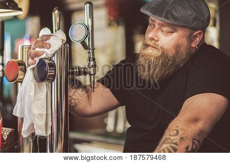 Pensive look. Portrait of fat man wiping beer taps thoughtfully. He standing at counter in pub sorrowfully