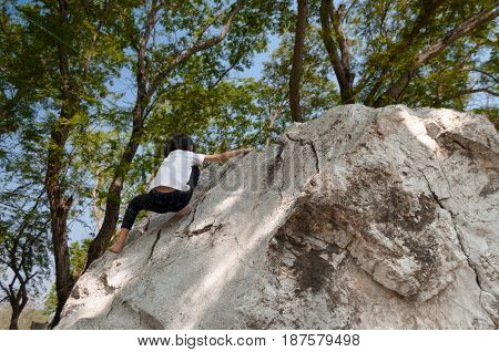Young asian girl climbing rock boulder barehanded.