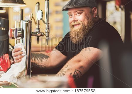 Enjoying work. Portrait of positive male bartender wiping beer taps with smile. He looking at camera with joy