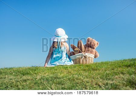 Girl in the hat with teddy bear in wicker basket having picnic on grass hill, having fun on sunny day, enjoying nature.