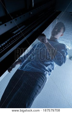At work. Pleasant nice good looking man standing in the server room and opening the grid metal door while doing the check of the network servers