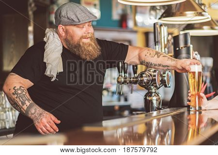 First client. Cheerful bearded man standing at counter while holding out glass of beer. He looking at mug with smile