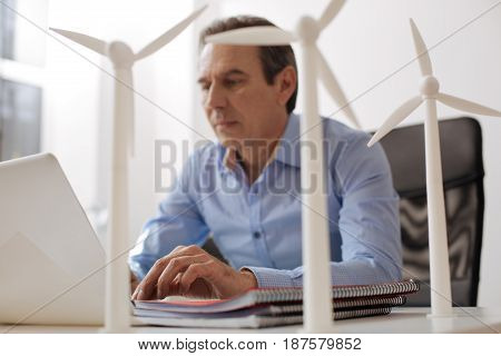 Start a new project. Pleasant professional engineer sitting at the table and building wind turbines while using laptop