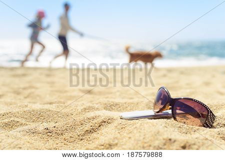 Close up sunglasses and phone on the beach with blurred people silhouttes on background running with dog.