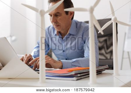 Plan to save the earth. Professional engineer sitting at the table and using laptop while elaborating wind turbines project
