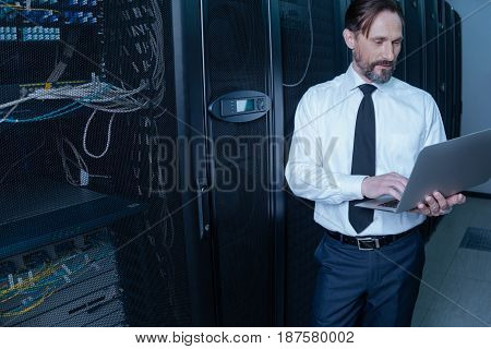 Professional programmer. Pleasant nice bearded man holding a laptop and looking at its screen while using it for work