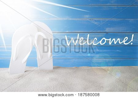 English Text Welcome. Sunny Summer Greeting Card With Sand And Flip Flops. Blue Vintage And Shabby Chic Wooden Background.