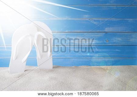 Copy Space For Advertisement Or Free Text. Sunny Summer Greeting Card With Sand And Flip Flops. Blue Vintage And Shabby Chic Wooden Background.