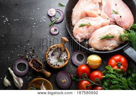 Raw chicken fillet with cooking ingredients on black slate table. Food background. Top view copy space.