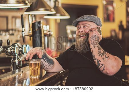 Lets talk. Pleasant cheerful guy laughing and sitting in pub while having conversation on mobile phone. He gesturing positively