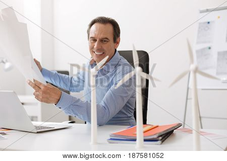 Eco life. Cheerful senior engineer sitting at the table and holding blueprint while looking at the model of wind turbines