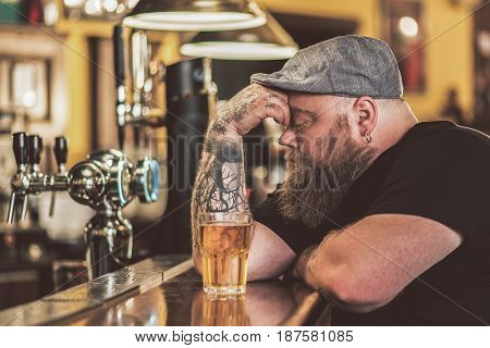 Feeling hopeless. Depressed obese bearded man keeping eyes closed and touching his face while leaning at bar counter. Glass of cold beer in front of him