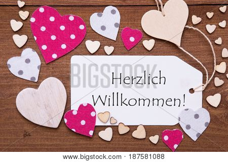 One Label With German Text Herzlich Willkommen Means Welcome. Flat Lay View With Wooden Vintage Background. Pink Wooden And Paper Hearts.